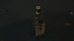 An empty bottle of liquor right outside my door